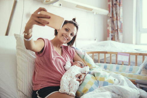 Mother taking a selfie with her newborn baby in hospital bed - MFF03980