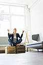 Businesswoman sitting on crate practising yoga - JOSF01754