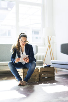 Businesswoman sitting on a crate using tablet - JOSF01757