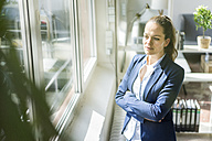 Businesswoman looking out of window - JOSF01766