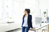 Businesswoman leaning on desk looking out of window - JOSF01769