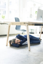 Businesswoman lying under the table in office sleeping - JOSF01775