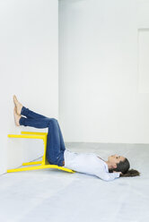 Woman lying on the floor with a yellow chair - JOSF01787