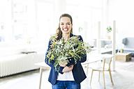 Portrait of happy businesswoman holding flowerpot - JOSF01796