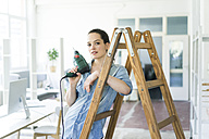 Portrait of woman at ladder holding electric drill - JOSF01799