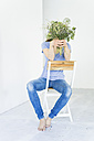 Woman sitting on a chair holding bunch of flowers in front of her face - JOSF01805