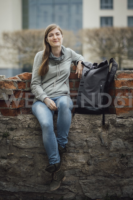 Portrait of smiling young woman sitting with her backpack on a wall - JSCF00006 - Jonathan Schöps/Westend61