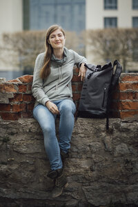 Portrait of smiling young woman sitting with her backpack on a wall - JSCF00006