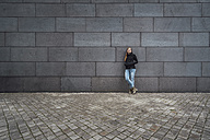 Young woman standing in front of grey facade waiting - JSCF00009