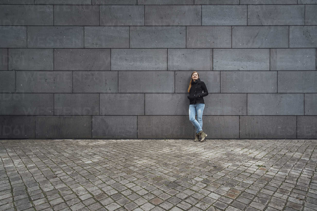 Young woman standing in front of grey facade waiting - JSCF00009 - Jonathan Schöps/Westend61