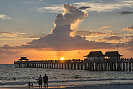 USA, Florida, Naples, silhouettes of Naples Pier and tourists with a huge rain cloud above during sunset - SH01964