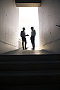 Two businessmen talking in a passageway - FKF02529