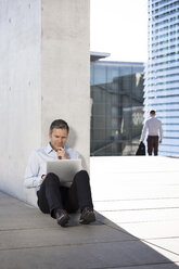 Businessman using laptop outdoors - FKF02532
