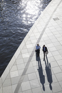 Two businessmen walking and talking at the riverbank - FKF02535