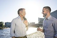 Two confident businessmen talking at the riverbank - FKF02541