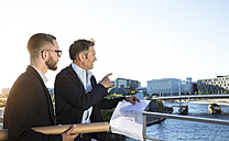Two architects with blueprint discussing on a bridge in the city - FKF02544