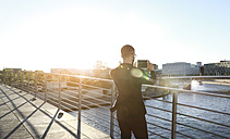 Businessman taking a picture with tablet on a bridge in the city - FKF02547