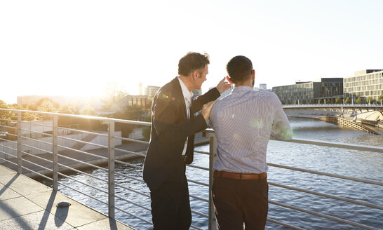 Two businessmen discussing on a bridge in the city - FKF02550