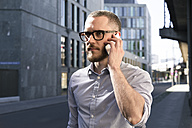 Businessman on cell phone in the city - FKF02559