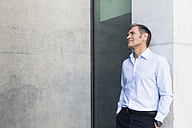 Mature businessman leaning against a wall - FKF02571