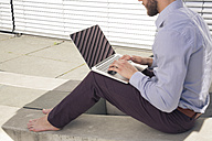 Barefoot businessman using laptop outdoors - FKF02580