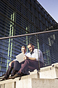 Two smiling businessmen sitting on stairs using laptop - FKF02589