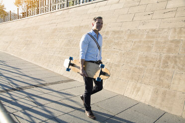 Businessman walking with skateboard - FKF02592
