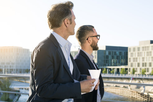 Two businessmen on a bridge in the city looking around - FKF02595