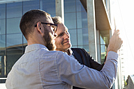 Two businessmen sharing a tablet outdoors - FKF02598
