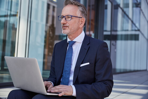 Portrait of businessman using laptop outdoors - SUF00285