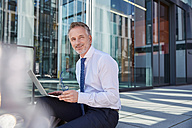 Portrait of smiling businessman using laptop outdoors - SUF00288