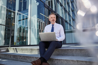 Portrait of businessman with laptop sitting on steps - SUF00291