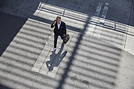 Businessman on the phone walking on pavement, top view - SUF00300