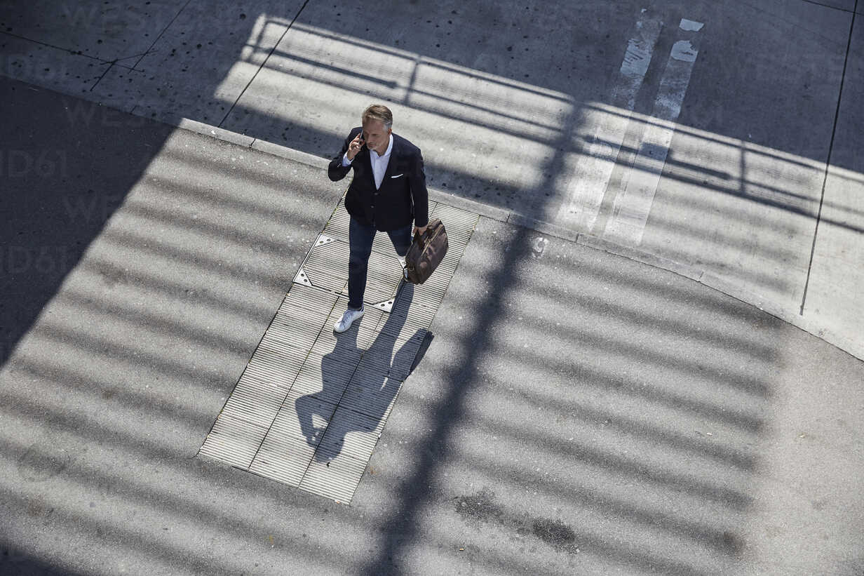 Businessman on the phone walking on pavement, top view - SUF00300 - Sullivan/Westend61