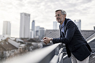 Grey-haired businessman standing on balcony looking over city - SBOF00731