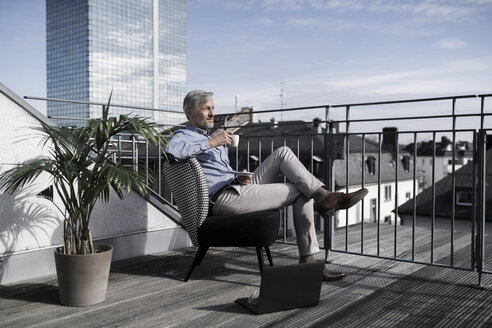 Grey-haired businessman sitting on balcony looking over city and drinking coffee - SBOF00734
