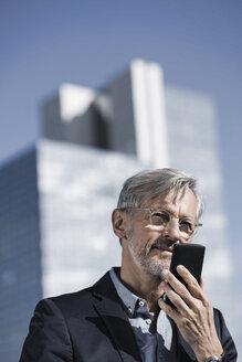 Grey-haired businessman speaking into smartphone - SBOF00737