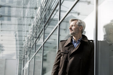 Grey-haired businessman standing at glass wall - SBOF00740