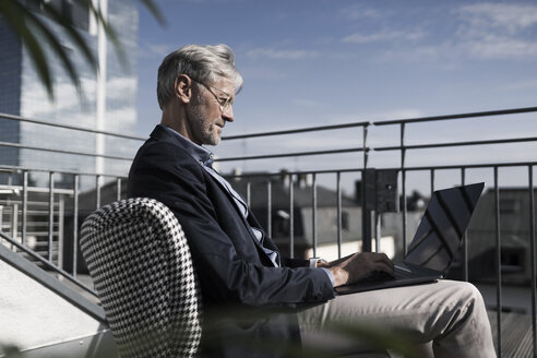 Grey-haired businessman sitting on balcony using laptop - SBOF00743