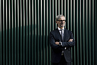 Portrait of grey-haired businessman in front of green wall - SBOF00749