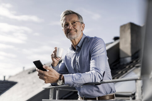Grey-haired businessman with smartphone standing on balkony drinking coffee - SBOF00755
