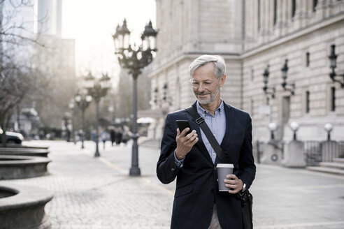 Grey-haired businessman in the city with smartphone and coffee to go - SBOF00764