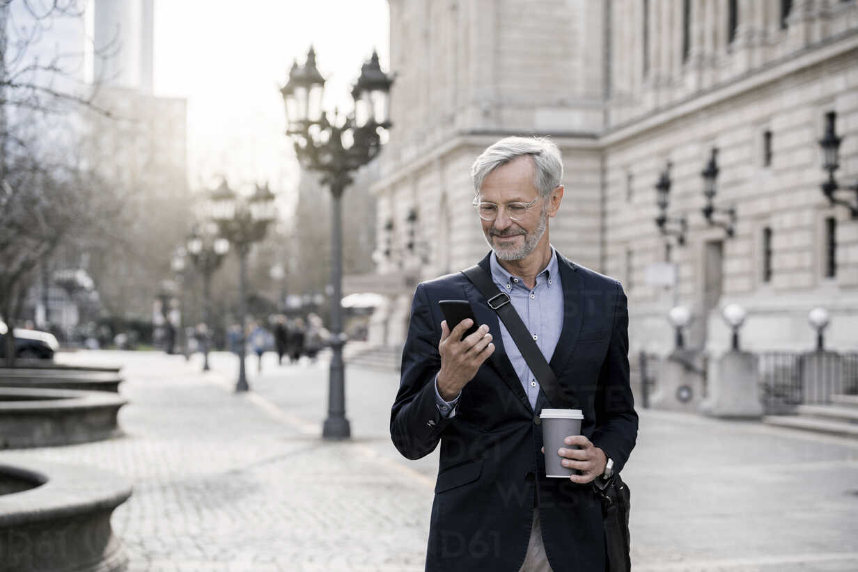 Grey-haired businessman in the city with smartphone and coffee to go - SBOF00764 - Steve Brookland/Westend61