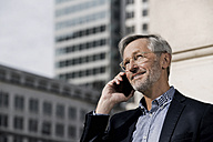 Grey-haired businessman on smartphone in the city - SBOF00767