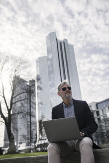 Grey-haired businessman with sunglasses working with laptop in park - SBOF00770