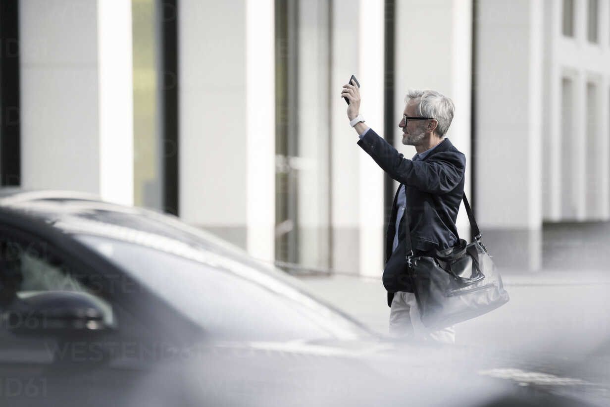 Grey-haired businessman calling a taxi in the city - SBOF00773 - Steve Brookland/Westend61