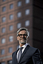 Grey-haired businessman in front of red skyscraper - SBOF00776