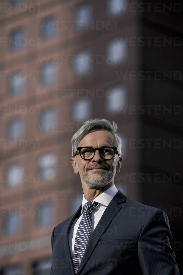 Grey-haired businessman in front of red skyscraper - SBOF00776 - Steve Brookland/Westend61