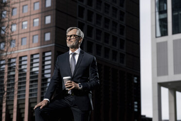 Grey-haired businessman in front of red skyscraper holding coffee to go - SBOF00779