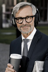 Grey-haired businessman with headphones and coffee to go looking into camera - SBOF00782